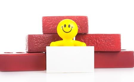 the little man: Un uomo giocattolo sorridente vicino a un mucchio di mattoni detiene il modulo di bianco puro. La costruzione concetto.
