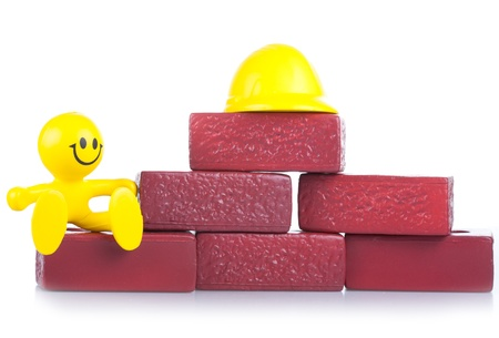petit bonhomme: One smiling toy little man near to a heap of bricks. The building concept.