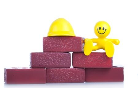 the little man: Sorridente un giocattolo piccolo uomo vicino a un mucchio di mattoni. Il concetto di costruzione.