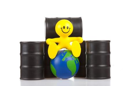 the little man: giocattolo sorridente piccolo uomo si siede accanto a mozziconi al petrolio del globo. Il concetto di supremazia mondiale di petrolio, l'estrazione delle aziende