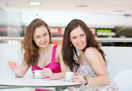 girl drinks coffee in cafe in shopping center photo