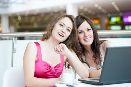 Two girls work on a laptop, sitting in cafe in shopping center photo