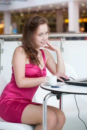 girl works on a laptop, sitting in cafe in shopping center photo