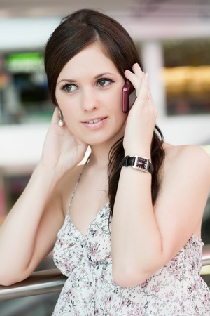 beautiful girl speaks by phone in shopping center photo