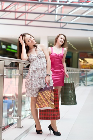Two friends with purchases in the big shopping center Stock Photo - 9918829