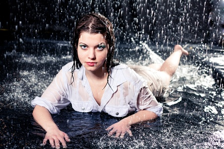 drenched: beautiful girl in the rain against a dark background Stock Photo