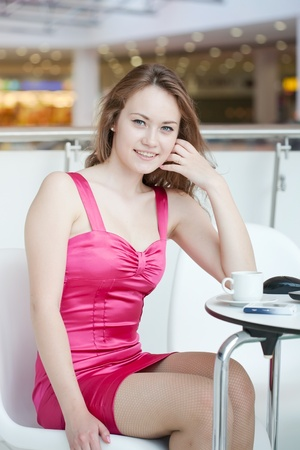 girl in a pink dress with a mobile phone in shopping center photo