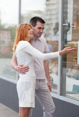 married couple to stand at a shop show-window. The woman shows on the pleasant thing. photo
