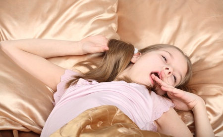 one teenage girl only: beautiful girl has woken up and lies in a bed with good mood