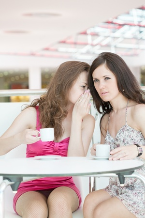Two girls sitting in cafe in shopping center photo