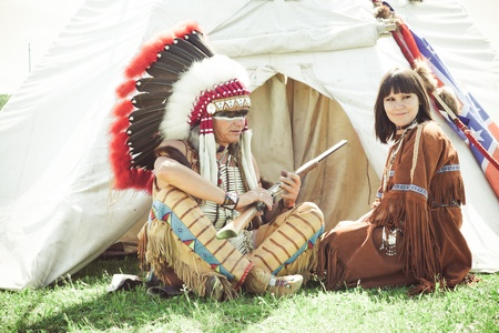 native american girl: North American Indians sit at a wigwam Stock Photo