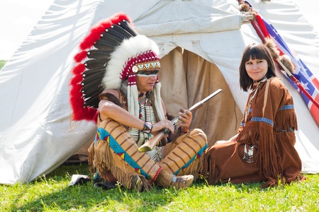 american indian: North American Indians sit at a wigwam Stock Photo