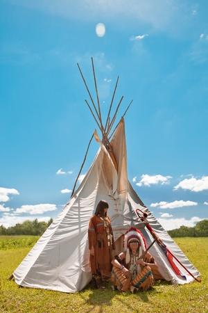Grupo de indios norteamericanos sobre un wigwam