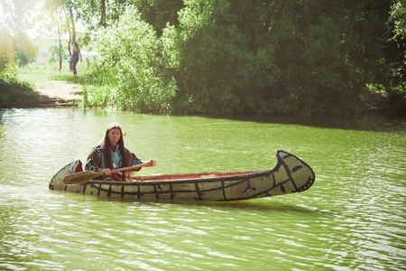 floats: North American Indian floats down the river on a canoe