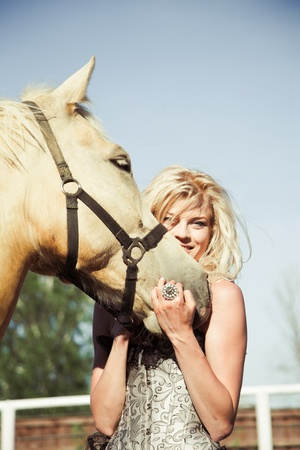 outdoor portrait of young beautiful woman with horse Stock Photo