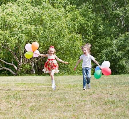 Happy girl and boy with balloons walking on the spring field photo