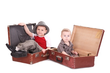 Two brothers sit in old suitcases photo