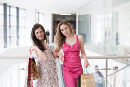 Two friends with purchases in the big shopping center photo