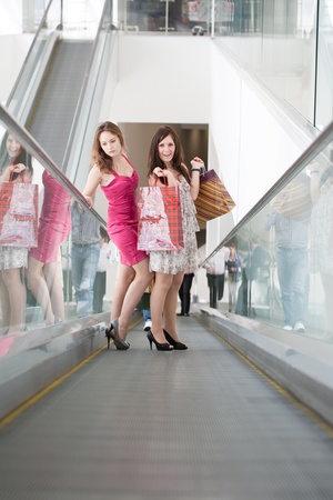 Two friends with purchases on the escalator in the big shopping center photo