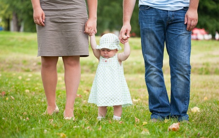 Beginning to go the child keeps for hands of parents photo