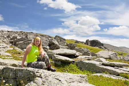 girl-tourist has a rest, sitting on stones photo