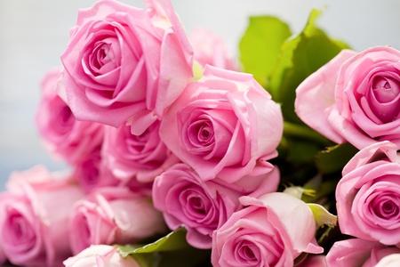 boeket van roze rozen ligt aan een zwembadzijde