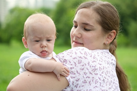 Young mum walks with the child in city park photo