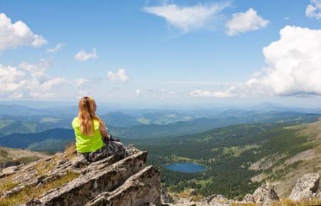 mujer se sienta en una roca y mira al lago de montaña Foto de archivo