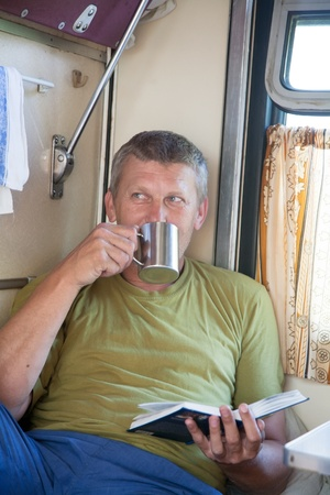 man goes in a train and reads the book photo