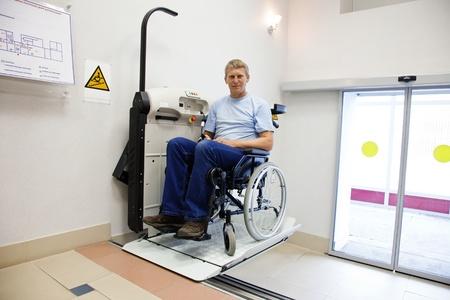 man in een ongeldige stoel loopt naar boven op de speciale verheffende apparaat Stockfoto