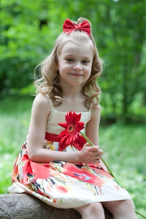smells: Portrait of the beautiful little girl with a red flower Stock Photo