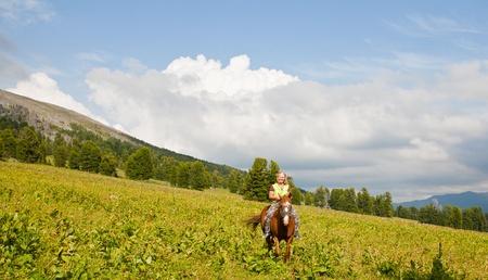 Female tourist on horseback at mountains photo