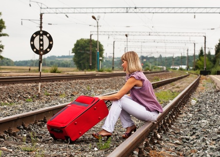 Girl on railway sitting with red  suitcase photo