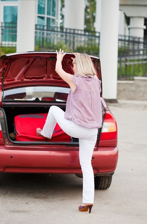 girl stacks a suitcase in a car luggage carrier photo