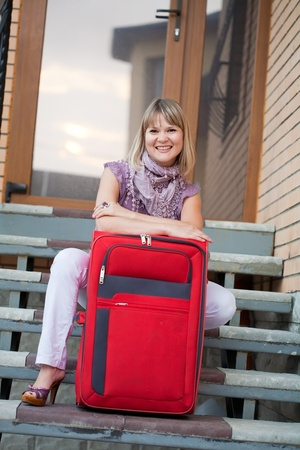 Happy woman with luggage on her home stages photo