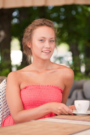 beautiful girl has a rest in street cafe in park photo