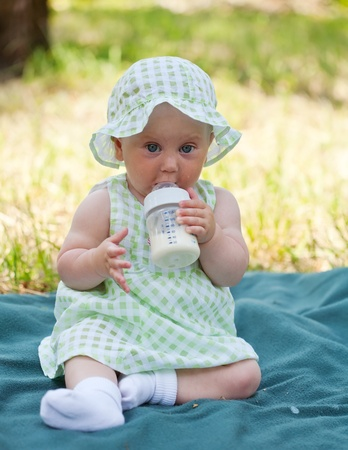 independently: little girl independently eats a dairy mix from a small bottle Stock Photo