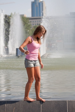 girl in a pink vest and shorts costs on a fountain side