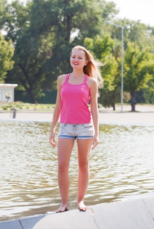 swarty: girl in a pink vest and shorts costs on a fountain side