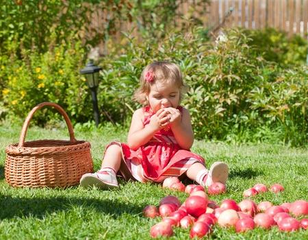 little girl eats an apple, sitting on a grass Stock Photo - 10881813