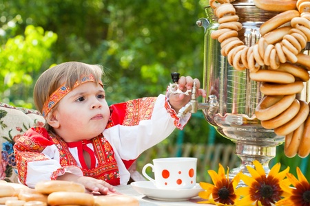 girl in Russian national dress drinks tea from a samovar photo
