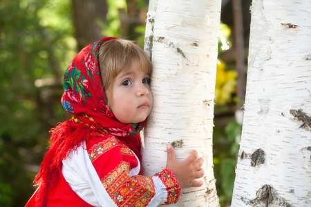 little girl in the Russian national dress embraces a birch photo