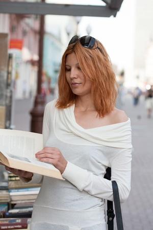 selects: ragazza sceglie il libro da negozio stradale.