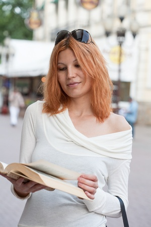 girl selects the book from street shop. photo