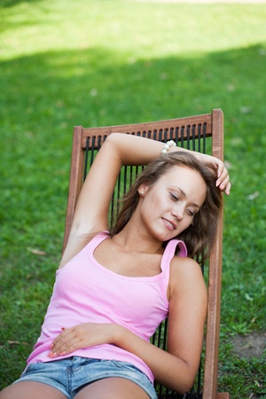 chaise lounge: girl has a rest sitting in a chaise lounge on a green grass