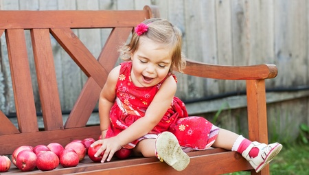 little girl in a summer dress sits on a wooden shop with apples photo