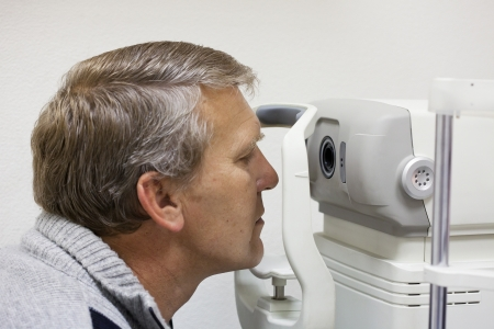 sight: mature man checks sight on the special device Stock Photo
