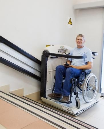 無効な椅子に男 2 階特別な昇降装置の上を歩く 写真素材