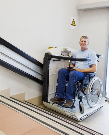 discapacidad: hombre en una silla de inv�lido camina arriba, en el dispositivo de elevaci�n especial