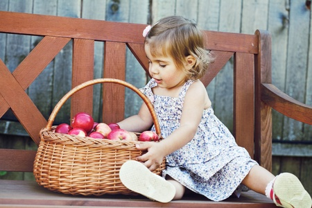 little girl sits on a bench with a basket of apples Stock Photo - 11008975